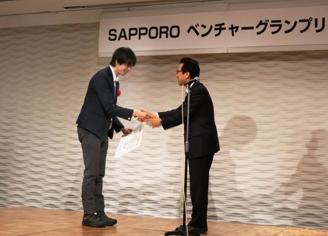 札幌市長・秋元氏より当社代表取締役の宮副へ賞状の授与。
